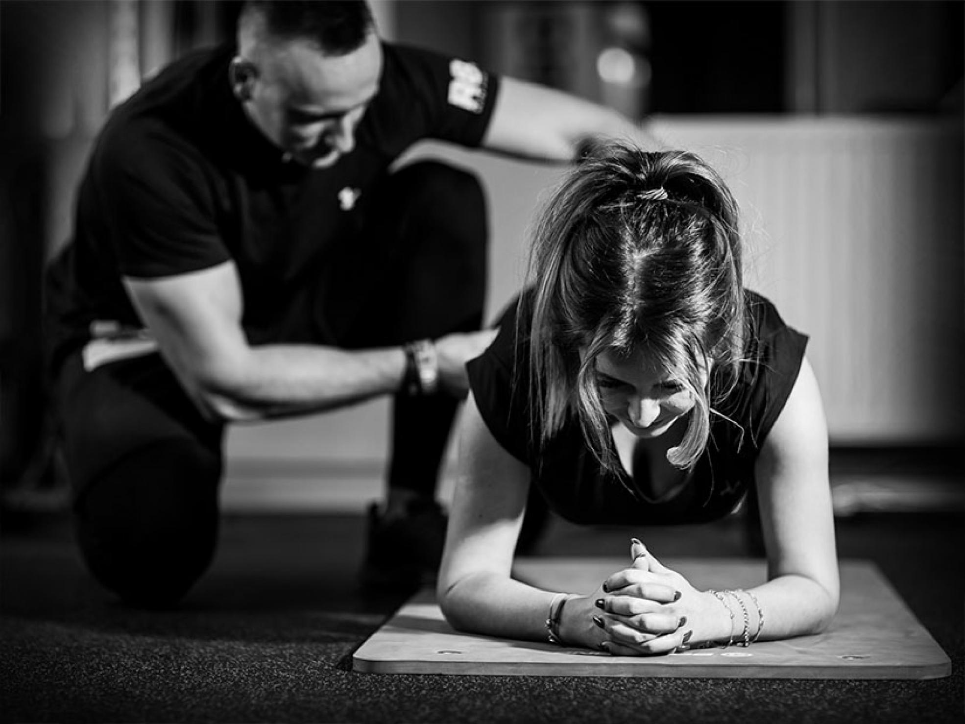 Kobieta ćwicząca podokiem trenera personalnego