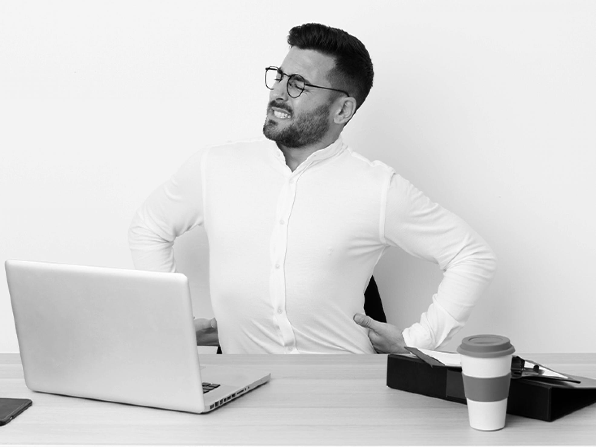 Mężczyzna przy biurku trzymający się zabolące plecy
