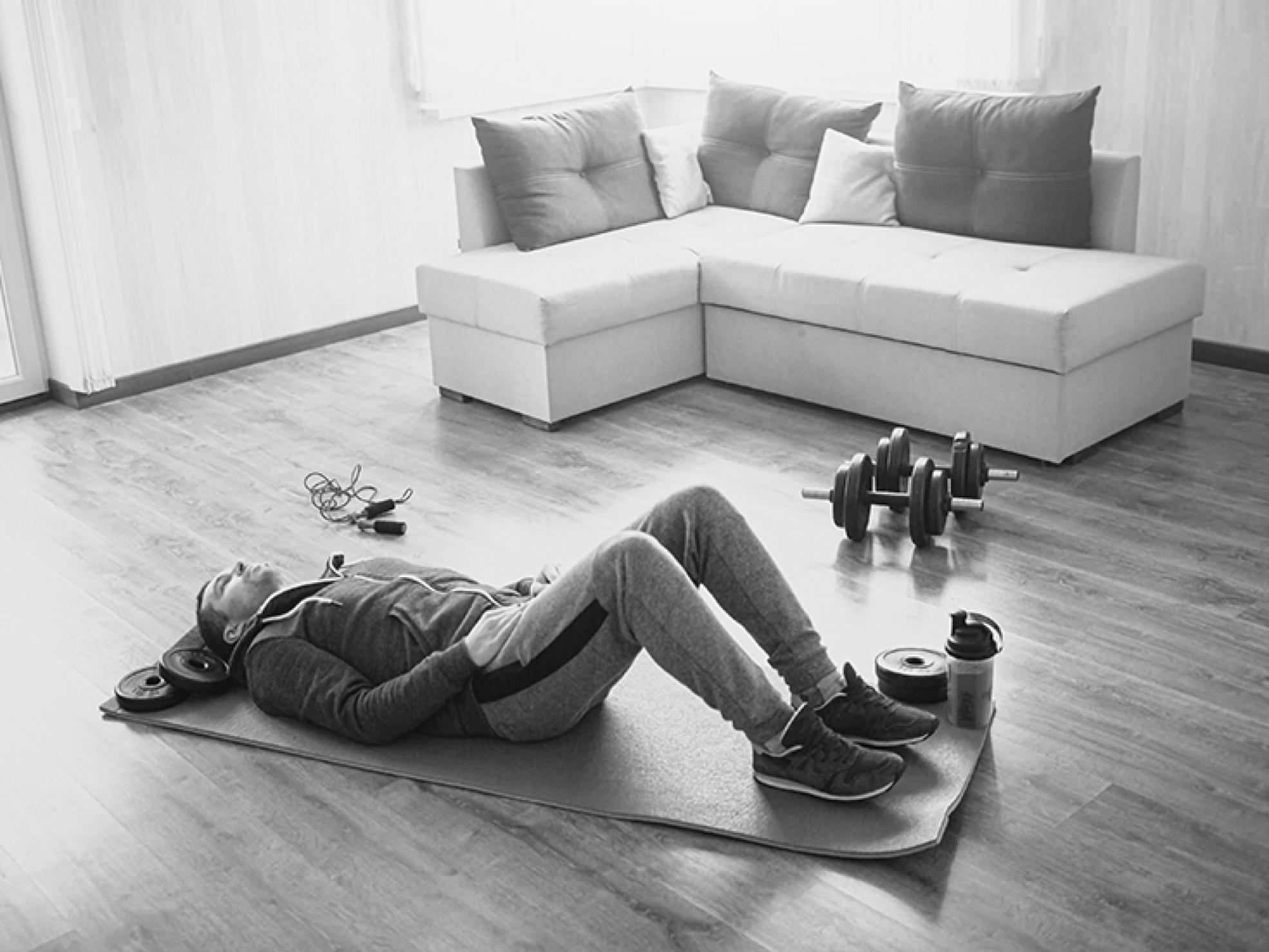 Mężczyzna odpoczywający namacie napodłodze poćwiczeniach - regeneracja