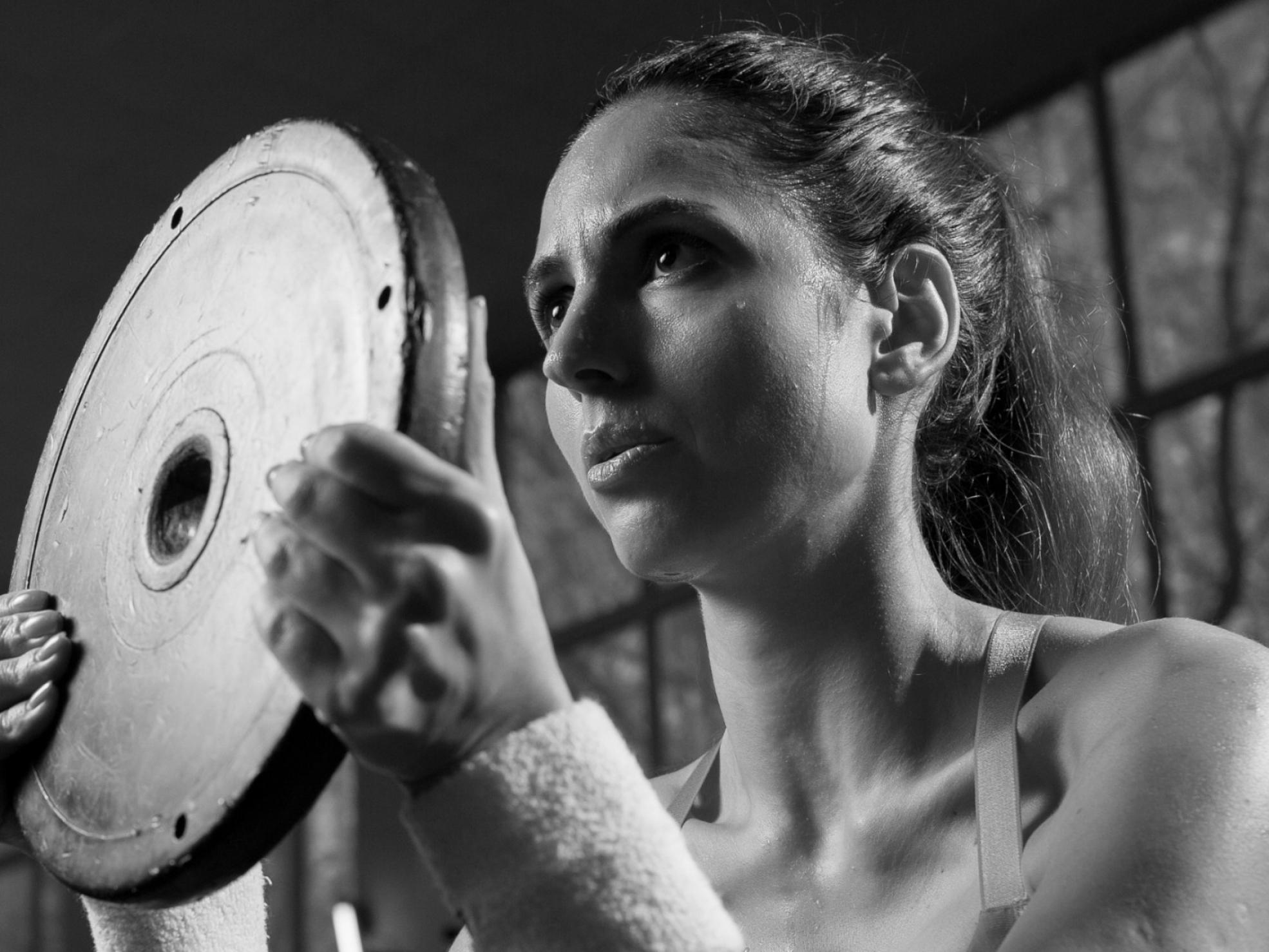 Kobieta ćwicząca zobciążnikiem nasiłowni - prawidłowy oddech