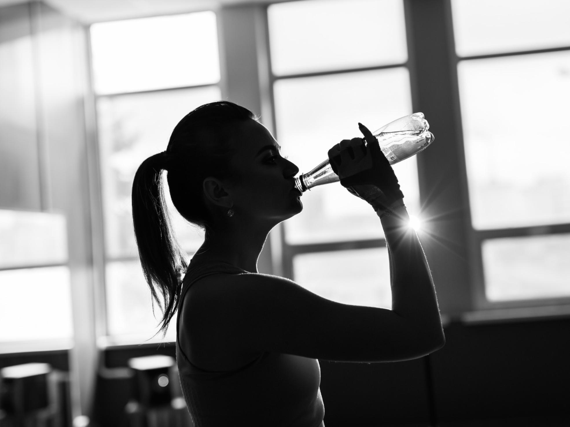 Młoda kobieta pijąca wodę podczas treningu nasiłowni - nawodnienie